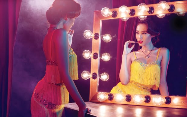 Stylised photo of a woman wearing a bright yellow, tasselled dress, standing in front of a theatrical mirror applying lipstick. She is wearing a Shine necklace.