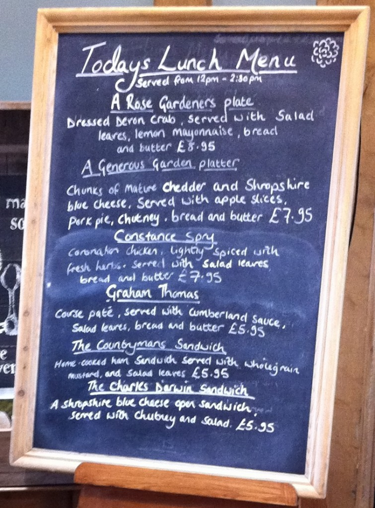 Photograph of a free-standing blackboard inside the door of the tearooms at David Austen's Plant Centre. Written on the blackboard in chalk is the title 'Today's Lunch Menu' with a selection of six main courses: A Rose Gardeners plate; A Generous Garden platter; Constance Spry; Graham Thomas; The Countrymans Sandwich; The Charles Darwin sandwich.