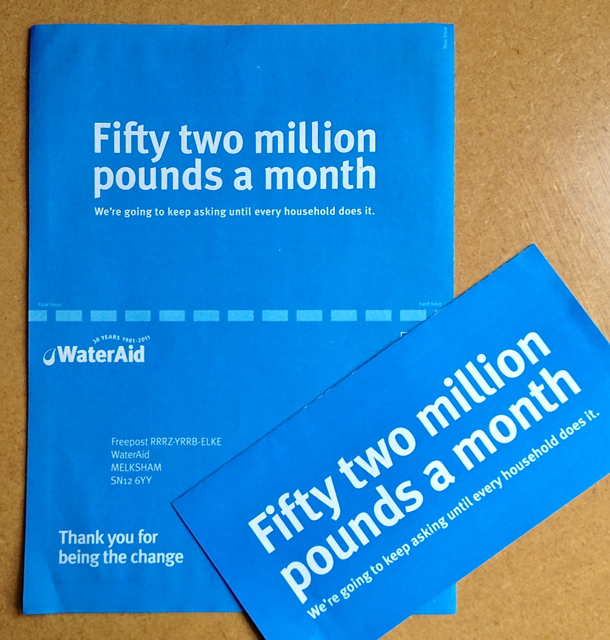 "Photograph of two information leaflets from WaterAid. One is almost A4 in size, the other is approximately the size of a DL envelope. Both are plain blue in colour with white writing that reads first in big lettering, ""Fifty two million pounds a month,"" then in smaller lettering underneath, ""We're going to keep asking until every household does it."""