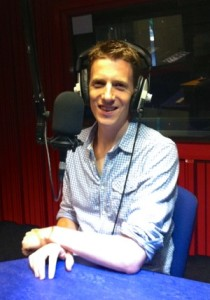 Photo of Matt sitting in front of a radio microphone and wearing headphones